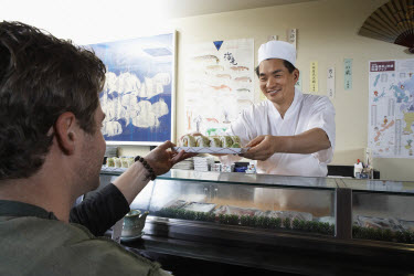 Sushi Chef handing Sushi to Customer over Sushi Bar