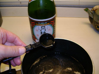 Adding sake to water in a pot for dashi
