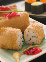 Inari Sushi with black sesame seeds and ginger garnish on white plate