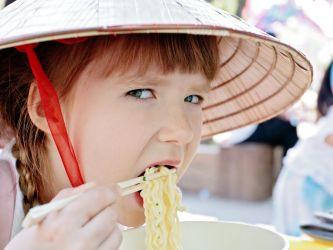 Girl eating noodles with chopsticks