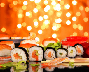 Maki Sushi on black table with fireworks in the background