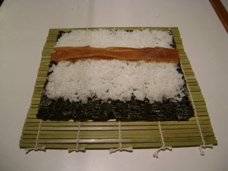 Laying seasoned kampyo gourd strips across sushi rice for futomaki