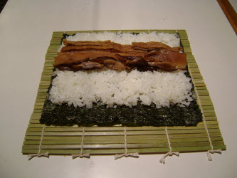Adding seasoned shitake mushrooms across rice for futomaki