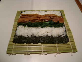 Adding spinach across sushi rice for futomaki