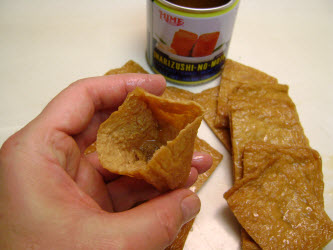 Opening the pocket of cooked and seasoned fried bean curd bag