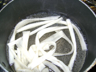 Boiling kampyo gourd strips in water for 10 minutes to soften