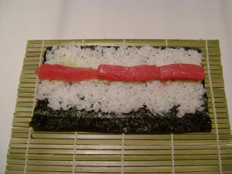 Adding tuna to hosomaki roll