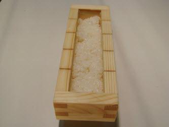 Putting 1/2 cup of rice in oshibako