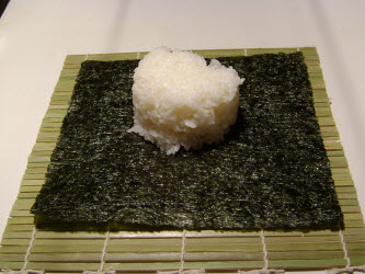 Placing 1 cup of rice on full sheet of nori for philadelphia roll