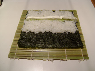 Adding a row of cream cheese across rice for philadelphia roll
