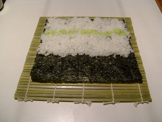 Swiping a row of wasabi across sushi rice