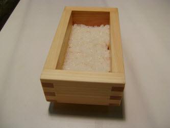 Adding 1/2 cup of rice to oshibako