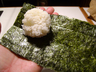 Place nori sheet in left hand and put 1/4 cup rice on it...