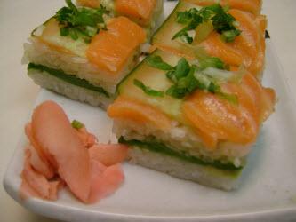 Finished salmon and cucumber oshi sushi on sushi plate