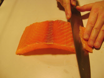 Slicing premium scottish salmon 1/8 inch thick at 45 degree angle for nigiri or sashimi