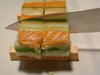 Now, slice across the oshi sushi...you can see I purposely made the cut past the cucumber to make the cut easier and so it will look better