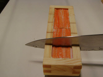 Slicing the oshi sushi using the grooves in the oshibako