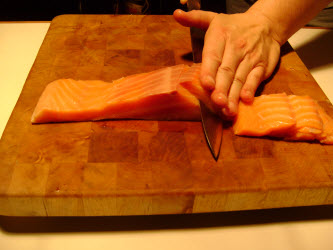 Slicing cold smoked salmon around 3/8 inch thick for maki sushi