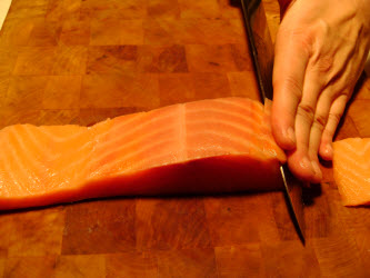 Slicing cold smoked salmon 1/8 inch thick at 45 degree angle for nigiri or sashimi