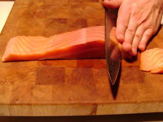 Slicing cold smoked salmon 1/8 inch thick at 45 degree angle for nigiri or sashimi
