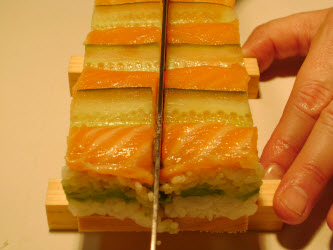 Take a very sharp wetted sushi knife and cut down the center lengthwise