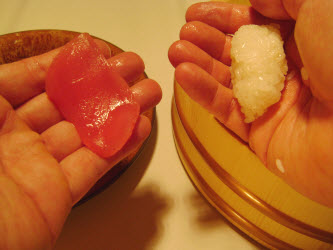 Picking up tuna in left hand and forming an oval with the sushi rice in the right hand