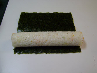Full sushi roll laying on the nori sheet