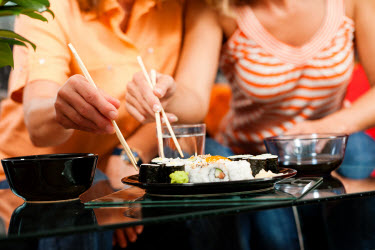 Couple sharing sushi and eating with chopsticks