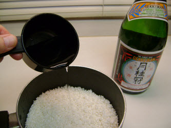 Adding sake/water mixture to rice in a pot