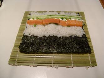 Adding cucumber to chumaki roll