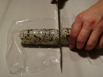 Lay saran wrap over the roll, wet your sushi knife and slice in the center