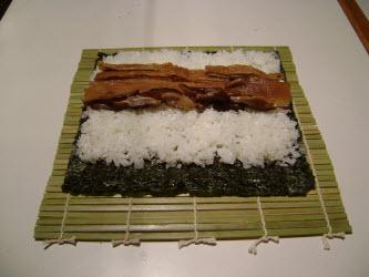 Adding seasoned shitake mushrooms across rice for futomaki