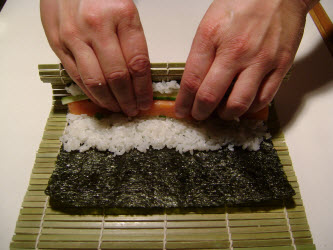 Put thumbs under the mat closest to you and lift up using fingers to hold fillings in place...