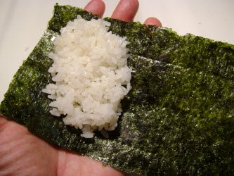 Spreading sushi rice out on nori for hand roll