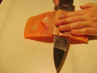 Trimming off outer brown part from premium scottish salmon