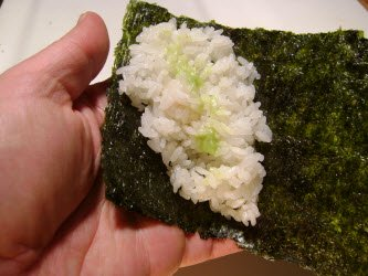 Adding a swipe of wasabi to sushi rice for hand roll