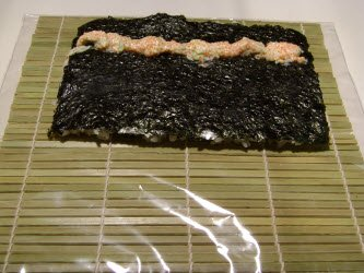 Flip the nori over and add a 1/4 of the roe-mayo sauce across the nori not centered but closer to you...