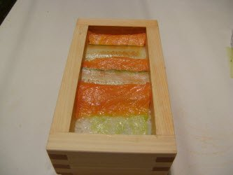 Starting at the far end of the oshi bako, layer a piece of salmon that has been cut to the width of the box...then overlap 1/2 of the salmon with cucumber...continue alternating till top is covered