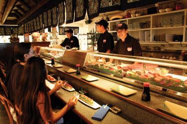 Customers at a sushi bar