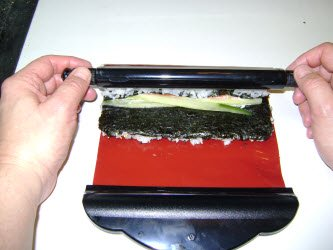 Bringing the bar up and over the ingredients till touches the nori closest to you...