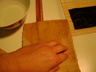 Tapping fingers on towel to remove excess vinegared water