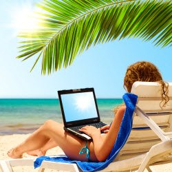 Woman working her business on a laptop on the Beach